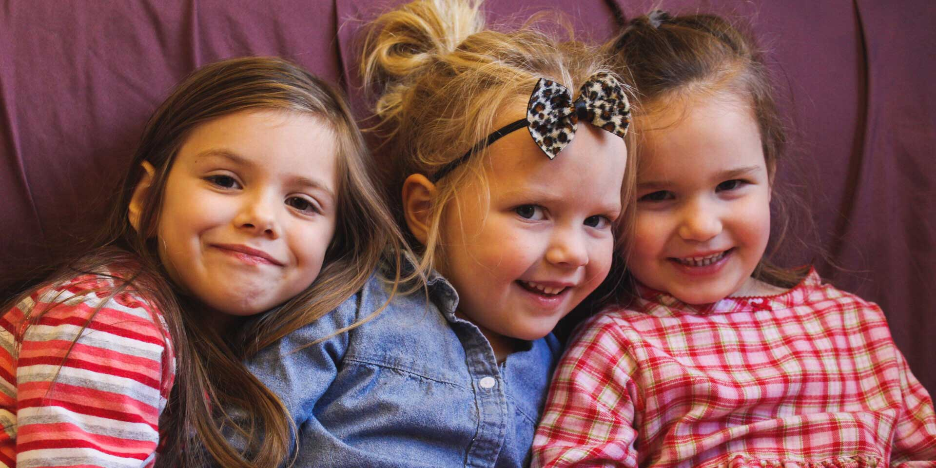 three toddler girls sitting on couch smiling