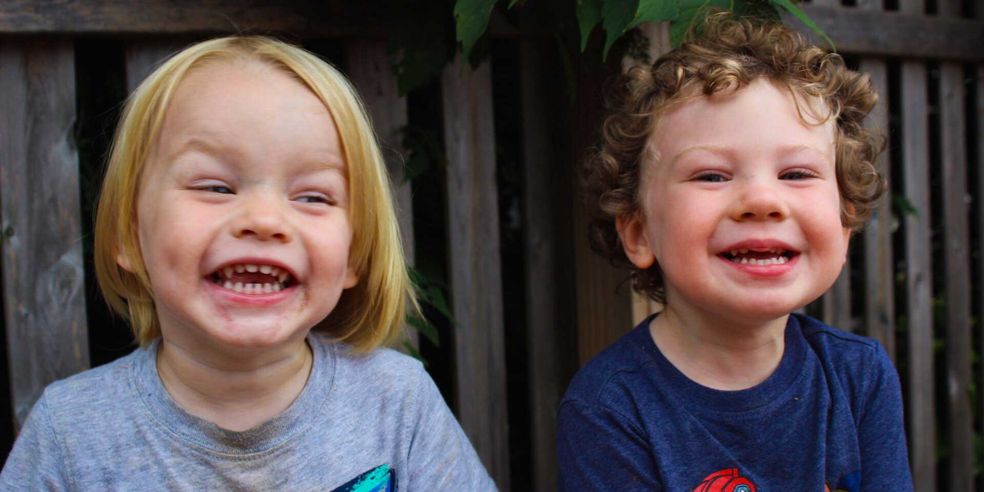 Two toddler boys laughing